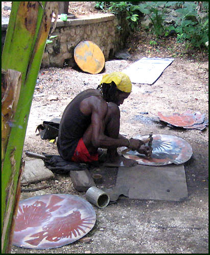 Cutting recycled steel drum in Haiti - Haitian metal tropical designs . - www.tropicdecor.com