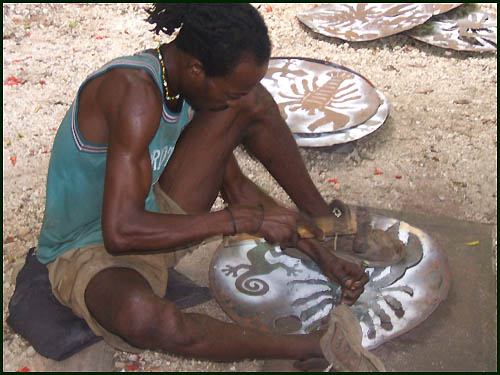 Cutting pattern into recycled steel drum in Haiti - Haitian metal tropical designs . - www.tropicdecor.com